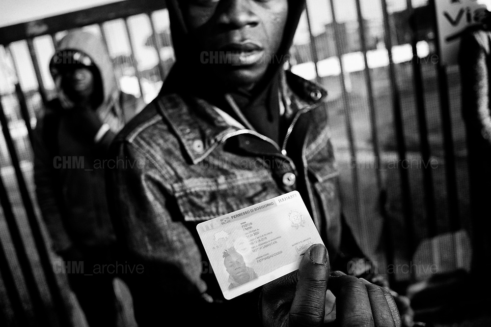 A migrant shows his residency permit during the evacuation of a former penicillin factory where migrants from Africa but also Italians, lived in precarious conditions, on December 10, 2018 on via Tiburtina in Rome. Christian Mantuano / OneShot