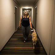 ARLINGTON, VA -JUNE3:  Tiffany Jolliff and her assistance dog, Railey, leave her apartment in Arlington, VA, June 3, 2016. The Washington Lawyers' Committee for Civil Rights and Urban Affairs filed a lawsuit Thursday in federal district court in the Eastern District of Virginia on behalf of Tiffany Jolliff against Uber, alleging violations of the Americans With Disabilities Act and the Virginians with Disabilities Act, alleging Uber unlawfully refused to accommodate Jolliff, who is blind, and her service dog, Railey. The complaint alleges that Jolliff, who works as a policy specialist for the federal government on employment for workers with disabilities, has been repeatedly discriminated against and denied Uber's services when Uber's drivers have seen that she is accompanied by her service dog Railey. Specifically, instead of accommodating her service dog Railey, as both the ADA and VDA require, Uber drivers have repeatedly driven off upon seeing that Ms. Jolliff had a service dog. (Photo by Evelyn Hockstein/For The Washington Post)