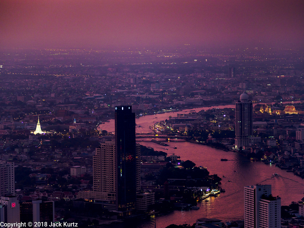 27 DECEMBER 2018 - BANGKOK, THAILAND: Looking north after sunset from the rooftop observation deck of the King Power Maha Nakhon Tower. The Chao Phraya River runs north to south through the frame. The lit up pagoda on the left is Wat Prayurawongsawat, a 19th century Buddhist temple. The MahaNakhon Skywalk, at the top of the King Power Maha Nakhon Tower, is 1,030 feet (314 meters) above street level. It is the tallest building and highest vantage point in Bangkok. The skywalk opened in November and has been drawing large crowds.    PHOTO BY JACK KURTZ