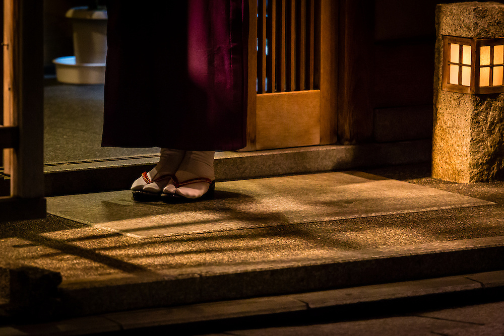 One of the traditional dressed women that work at the restaurants and tea houses at the Gion district of Kyoto, waits patiently at the entrance.