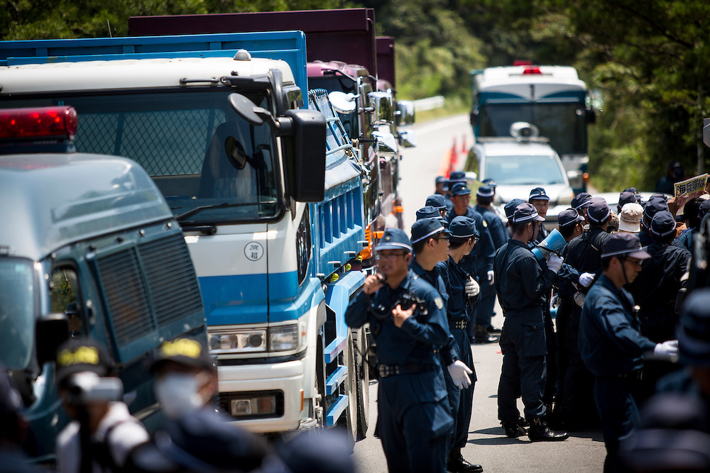 OKINAWA, JAPAN - AUGUST 19 : Trucks loaded of construction materials passing as they guard the Anti U.S base protesters after staging a sit-in protest against the construction of helipads in front of the gate of U.S. military's Northern Training Area in the village of Higashi, Okinawa Prefecture, on August 19, 2016. Japanese government resume construction of total six helipads in a fragile ten million year old Yanbaru forest that is home to endemic endangered species such as the Okinawan rail and Okinawan wood pecker. (Photo by Richard Atrero de Guzman/NURPhoto)