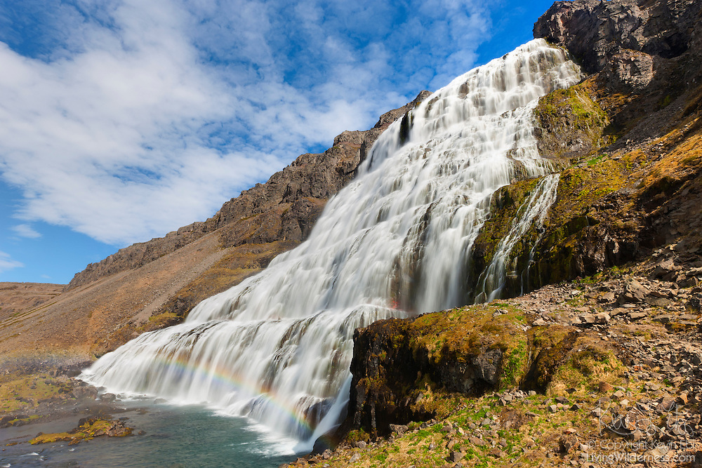 A rainbow forms in the bottom tier of Dynjandi, a waterfall located in the northwestern fjords of Iceland. Dynjandi is the tallest waterfall in the region, with a height of 200 feet (61 meters). It is nicknamed wedding cake falls because its tiers are wider at the bottom than at the top. The top of the waterfall is about 98 feet (30 meters) wide; the bottom tier is 196 feet (60 meters) wide.