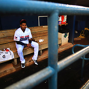 Toledo's Argenis Diaz sits in the dugout before heading out on the field after a rain delay before a baseball game between the Toledo Mud Hens and Columbus Clippers at Fifth Third Field on Friday, June 30, 2017. THE BLADE/KURT STEISS