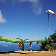 A tandem hang glider prepares to take off above the hillside of Pedro Bonita high in the hills of Rio de Janeiro. Pilots of hang gliders and para gliders take tourists for tandem flights with breathtaking views of the city before landing on Sao Conrado beach. Rio de Janeiro,  Brazil. 9th September 2010. Photo Tim Clayton.