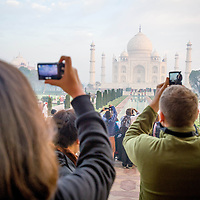Feb 12, 2013 - Tourists try to capture a clear image of the Taj Mahal through the smog in Agra, India. To cut back on pollution, cars and buses are not allowed to drive to the Taj Mahal but to a parking lot about 1.5 miles away, where visitors can take battery-run buses or horse-drawn carriages to reach the monument.<br /> <br /> Story Summary: It is said that the battle over global warming is to be won or lost in Asia. With growing populations and new economic boom in the global markets across Asia countries like India, Nepal and Cambodia have to grapple with the success and the environmental disaster that comes with ramped up production in unchecked or unregulated industries to compete in todays marketplace. The catastrophic air pollution makes for new problems to be dealt with such as a future health crisis, quality of life issues and the tarnished image of reduced visibility to world heritage sites for tourism.