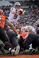 New Orleans Saints quarterback Drew Brees (9) leaps the line of scrimmage to score a touchdown during the second half of an NFL football game against the Bengals in Cincinnati, Oh, Sunday, Nov. 11, 2018. (AP Photo/Bryan Woolston)
