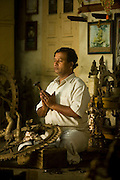 Master craftsman Radhakhrishna Stpathy, works on the final touches to a statue of the dancing Nataraja at dawn in his workshop in Swamimalai, India.The current Stpathy family is the twenty third generation of bronze casters dating back to the founding of the Chola Empire. The Stapathys had been sculptors of stone idols at the time of Rajaraja 1 (AD985-1014) but were called to Tanjore to learn bronze casting. Their methods using the ,?Úlost wax,?Ù process remains unchanged to this day..
