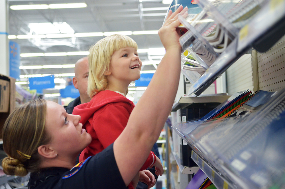 Sgt. Ashley Ruple lifts Alexis Tischer, 5, so she could look at notebooks on Thursday during the Petal Police Department's Shop with a Cop event at Walmart. The program helped twelve children from 5 families.  Bryant Hawkins/ Hattiesburg American