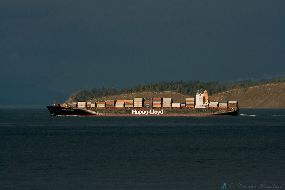 Hapag-Lloy container ship Kobe Express departing the Puget Sound, with Whidbey Island and the San Juan Islands in the background under a stormy sky