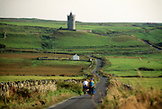 Ireland, County Clare, Bunratty, bicyclists cycling through countryside.