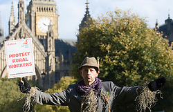 © Licensed to London News Pictures. 25/10/2011. London, UK. Horticultural worker Dave Hide from horsham, West Sussex holding a 'Protect Rural Workers' placard. Press call for Rural workers dressed as scarecrows to raise awareness for over 150,000 agricultural workers who face diminishing pay and working conditions if the agricultural wages board is abolished. Photo credit: Ben Cawthra/LNP