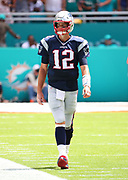 Sep 15, 2019; Miami Gardens, FL, USA;  New England Patriots quarterback Tom Brady (12) walks the sideline during an NFL game against the Miami Dolphins at Hard Rock Stadium in Miami Gardens, FL. The Patriots beat the Dolphins 43-0. (Steve Jacobson/Image of Sport)