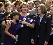 FILE--YEAR END PICTURES--Ellen Saracini, center, holds an American Flag that was presented to her by a Naval Honor Guard, as her daughters, Brielle, left, and Kirsten, right, stand beside her, after a memorial service for their husband, and father, pilot Victor J. Saracini, in Newtown, Pa., Tuesday, Sept. 18, 2001. Saracini was the pilot of United Airlines Flight 175 that was hijacked and crashed into the World Trade Center in New York, last Tuesday. (Photo by William Thomas Cain/photodx.com)