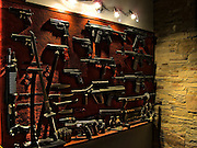 A wall display of a collection of guns, rifles and swords