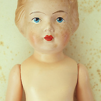 Head and chest of vintage female doll with face slightly freckled from ageing lying naked on antique paper