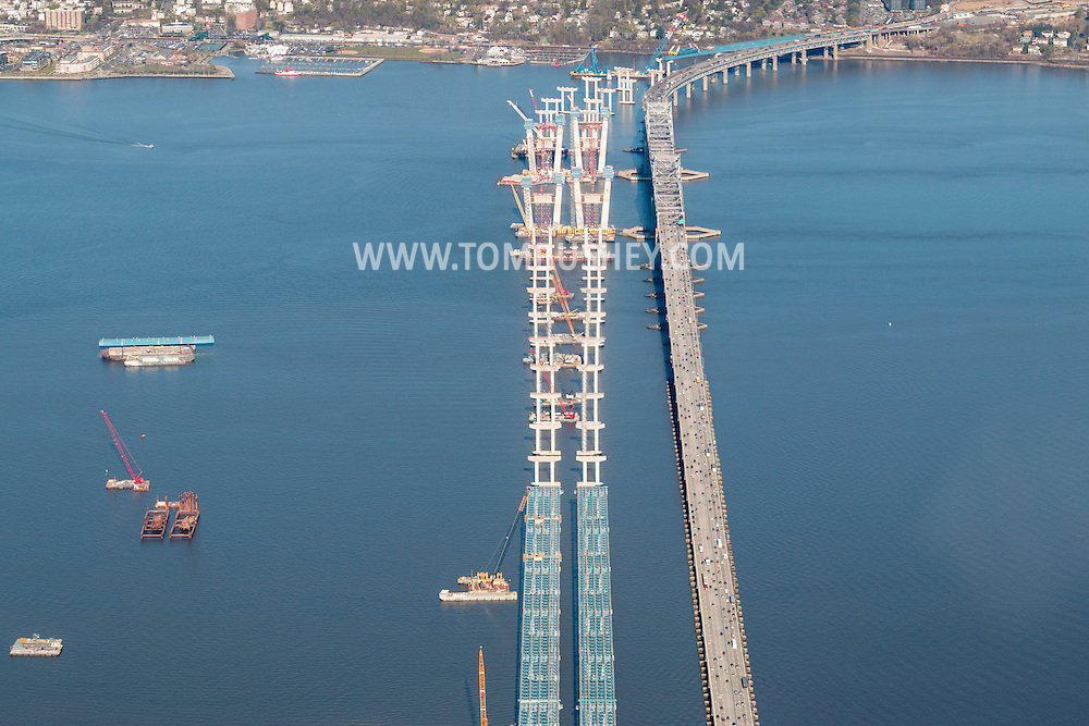 Tarrytown, New York - Construction continues on the new Tappan Zee Bridge, at left, over the Hudson River as traffic drives on the current bridge on April 20, 2016. The bridge connects South Nyack in Rockland County and Tarrytown, at top of frame, in Westchester County.