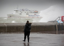 © Licensed to London News Pictures. 09/02/2020. Portsmouth, UK. A woman, soaking wet from the waves during high tide at Southsea, Portsmouth watches as a Brittany Ferry passes as Storm Ciara batters the UK. Airlines have cancelled dozens of domestic and international flights as the storm brings strong winds and rain. Photo credit: Peter Macdiarmid/LNP