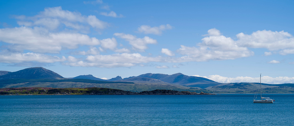Moored yacht with Isle of Arran in distance viewed from Kintyre, Argyll coast, Scotland