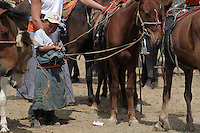 Liten mongolsk gutt holder hestene i pausen undre det mongolske mesterskapet i polo, small mongolian boy holds the horses in a break during the mongolian championship in polo