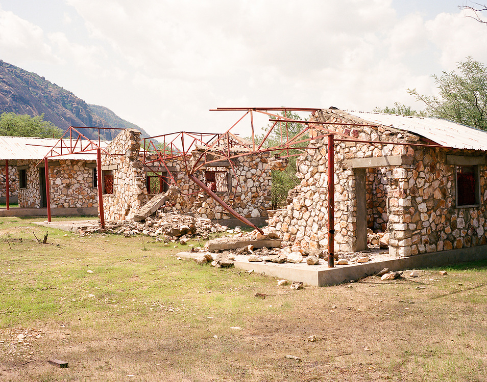 """NUBA MOUNTAINS, SUDAN – JUNE 9, 2018: The remains of student dormitories stand untouched after a 2014 bombing destroyed much of Hieban Bible Institute. During the bombing, six children from the same family were killed when a parachute bomb dropped near the Institute's entrance. Four other adults also perished nearby from bombs dropped by high flying cargo planes repurposed by the Sudan Armed Forces, which regularly carry out inaccurate but devastating bombing campaigns in predominantly civilian areas.<br /> <br /> In 2011, the government of Sudan expelled all humanitarian groups from the country's Nuba Mountains. Since then, the Antonov aircraft has terrorized the Nuba people, dropping more than 4,080 bombs on hospitals, schools, marketplaces and churches. Today, vestiges of the Antonov riddle the landscapes of daily life, where more than 1 million Nuba live in famine conditions – quietly enduring the humanitarian blockade intended to drive them out of the region. The skies are mostly clear. Yet the collective memory of the bombings remains an open wound, and the Antonov itself a persistent threat. So frequent were the attacks that the Nuba nicknamed the high flying aircraft and its dismal hum: """"Gafal-nia ja,"""" they would declare, running to the hillsides. """"The loss of appetite has come."""""""