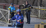 WASHINGTON (Jan 4, 2017) -- A U.S Park Police Officer escorts bicyclists from the towpath area where a suspiciously stashed violin case was found containing two firearms, near Fletcher's Cove Boathouse on the C&O Canal late Wednesday morning Jan. 4, 2017.  More guns and ammunition were also found around the area.  Photo by Johnny Bivera