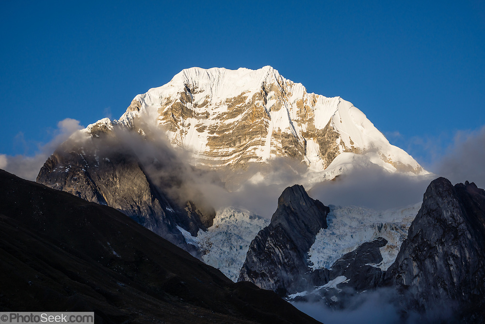 "East Face of Siula Grande (20,814 ft or 6344 m) at sunrise in the Cordillera Huayhuash, Andes Mountains, Peru, South America. Day 3 of 9 days trekking around the Cordillera Huayhuash. Siula Grande was the subject of the gripping 2003 British docudrama ""Touching the Void."" In 1985, climbers Joe Simpson and Simon Yates scaled the treacherous West Face of Siula Grande, but after Joe broke his leg, their descent became one of the most amazing survival stories in mountaineering history. The 2003 movie is based upon Joe Simpson's harrowing book, ""Touching the Void: The True Story of One Man's Miraculous Survival."""