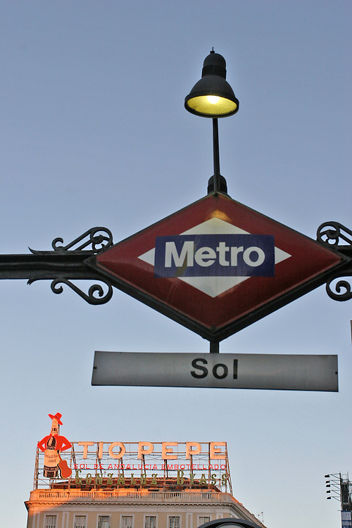 Puerta del Sol subway station in Madrid, wit the famous Tio Pepe neon sign in the background.