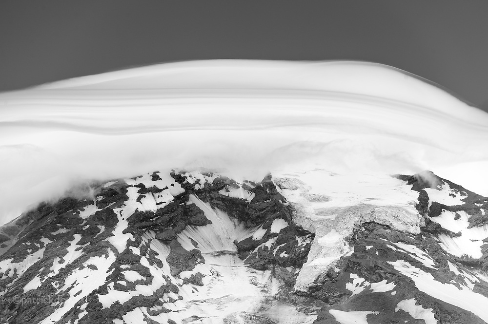"""Tight shot of the top of Mt. Rainier, under a lenticular """"cap"""" cloud. You can see one of the glaciers clearly ... the thickest glacier on the mountain is over 700 feet thick. http://www.gorp.com/parks-guide/travel-ta-mount-rainier-national-park-glaciers-sidwcmdev_067752.html Lenticular """"cap"""" cloud over Mt. Rainier"""