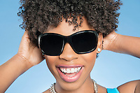 Close-up of cheerful young woman wearing sunglasses with hands behind head over colored background