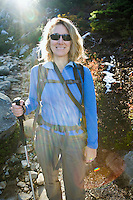 Middle aged woman posing for a portrait on a mountain trail with the sun flaring in from behind.