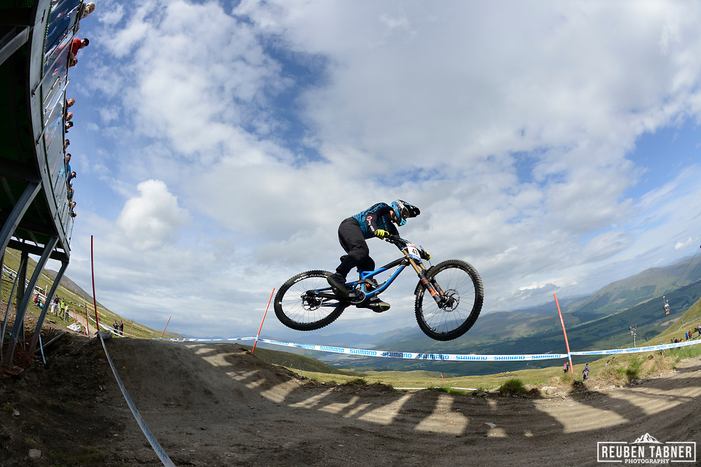 Francisco Pardal grabs some air whilst crowds watch from above at the top of the Fort WIlliam downhill track during Saturday practise at the UCI Mountain Bike World Cup.