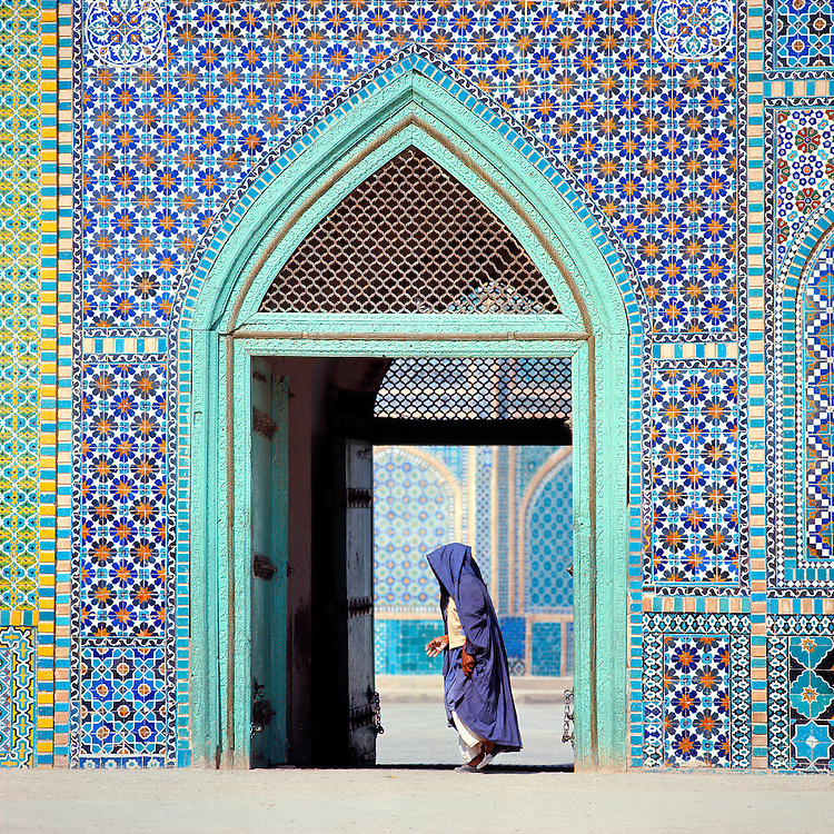 A pilgrim walks in front of an ornately tiled entry to the Shrine to Hazrat Ali, in Mazar-i-Sharif, Afghanistan.