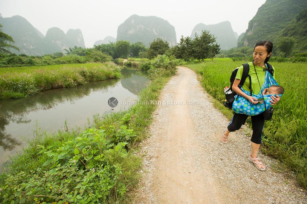 A woman carrying a baby walks down a gravel road in Yangshuo, China (Model Released, Rachel Ouyang, Tintin Ouyang).
