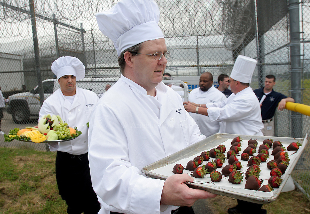 (060607  Billerica, MA) Paul Marren, a graduate of the Inmate Culinary Arts Program at the Billerica House of Correction, carries out chocolate-covered strawberries for the luncheon following the graduation, Wednesday,  June 6, 2007.    Staff photo by Angela Rowlings.