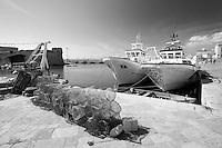 Nasse depositate sulla banchina del porto pescerecci di Gallipoli (LE), dietro due paranze ormeggiate di fronte al Rivellino