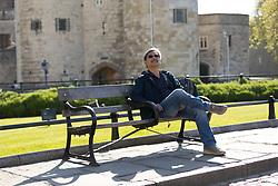 © Licensed to London News Pictures. 05/05/2018. London, UK. A man relaxes on a bench in front of the Tower of London during hot and sunny weather near the River Thames in London this morning. Photo credit: Vickie Flores/LNP