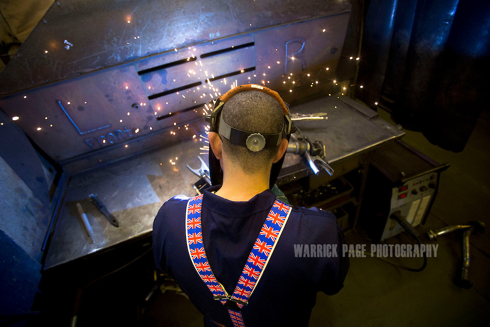 A factory worker wearing Union Jack suspenders, welds components at the BM Catalysts factory on February 6, 2013, in Mansfield, England. (Photo by Warrick Page)