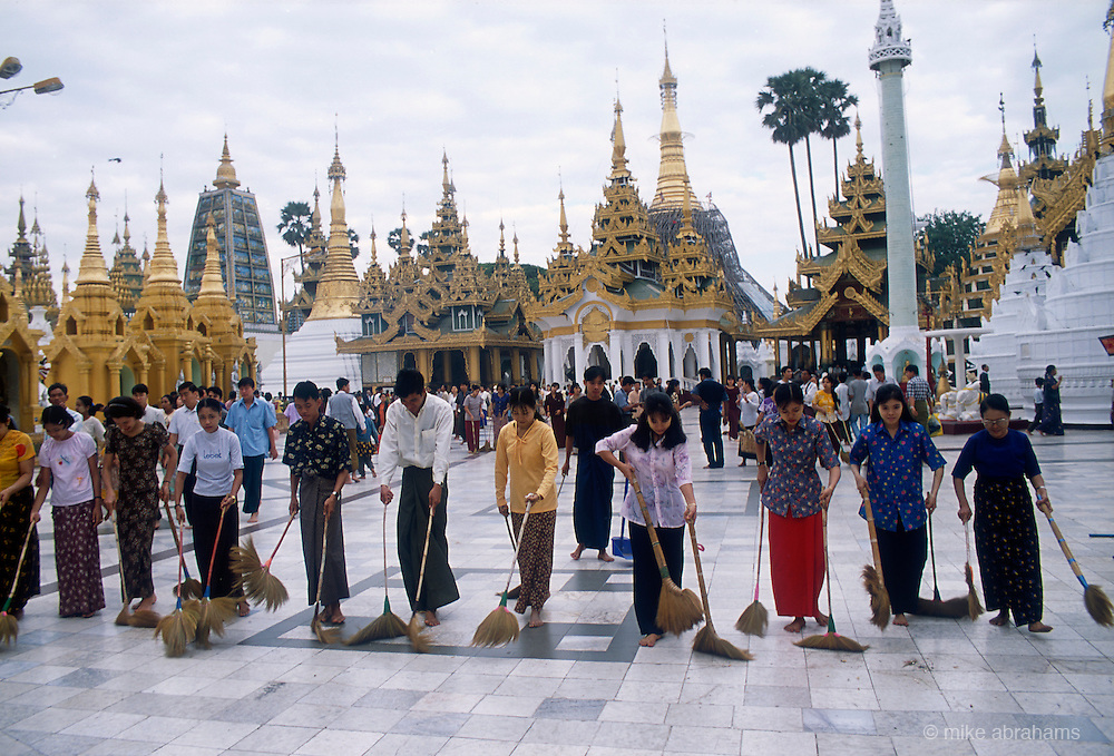 Cleaners sweeping through Shwedagon Paya, the most important Buddist temple in Rangoon. Nearly 100 metres high. Decorated with 8000 gold plates, 5000 diamonds and 2000 other precious and semi precious stones and surrounded by 82 smaller temples, attracts the faithful day and night.<br /> Rangoon, Burma. 1999