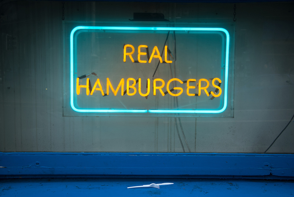 Used cutlery and a neon sign advertising real hamburgers in Dublin, Ireland.