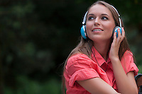 Beautiful young woman listening to headphones in park