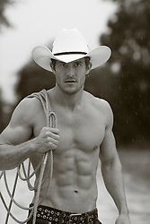 shirtless hunky cowboy in the rain on a ranch
