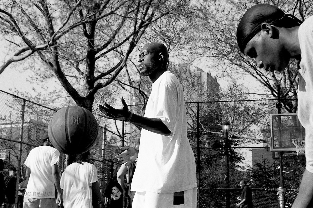 """April 24th 2008. New York, New York. United States..Located in the heart of Greenwich Village, the West 4th Street basketball Court, known as """"The Cage"""", offers no seating but attracts the best players and a lot of spectators as soon as spring is around the corner..Half the size of a regular basketball court, it creates a fast, high level of play. The more people watch, the more intense the games get. « The Cage » is a free show. Amazing actions, insults and fights sometimes, create tensions among and inside the teams. The strongest impose their rules. Charisma is present..""""The Cage"""" is a microcosm. It's a meeting point for the African American street culture of New York. Often originally from Jamaica or other islands of the Caribbean, they hang out, talk, joke, laugh, comment the game, smoke… Whether they play or not, they're here, inside """"The Cage"""". Everybody knows everybody, they all greet each other, they shake hands and hug: """"Yo, whasup man?"""""""