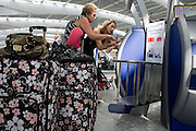 Departing passengers use British Airways self-service check-in kiosks at Heathrow Airport's Terminal 5.