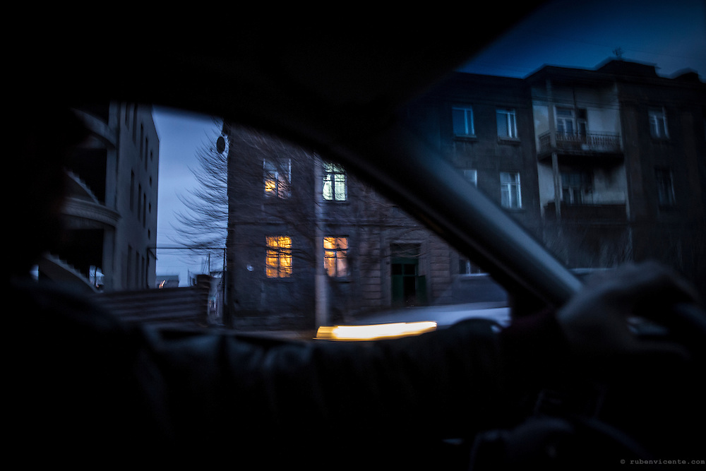 As the sun sets, warm lights are turned on in the old soviet era buildings in the city of Gyumri. Armenia