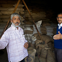 Rupesh (left) discusses the running of the Atri Block State Food Corporation Godown (depot) in Atri with assistant manager  Bharat Rai...In the course of his work, Rupesh (no surname), advisor to the Indian Supreme Court Commissioner on the right to food, made an unannounced visit to the Atri Block State Food Corporation Godown (depot) in Atri where he unearthed two cases of malpractice. He found that Bharat Rai, assistant manager of the godown, responsible, among other things, for the distribution of one quintel of grain per-month to each of the PDS (Public Distribution System) retailers in his area as part of the Antyodaya scheme (providing staple food for the poorest of the poor), had failed to deliver this essential food for eleven of the previous twelve months. Furthermore, it was discovered that though retailers supplied by the Atri Godown had paid Rai for grains for the months of November and December 2010, these foods had not in fact been delivered. Rupesh demanded paperwork from Bharat Rai and will now take up the case with the District Magistrate in Gaya. Rupesh argues that the only way to properly administer schemes like PDS is to make them universal so that the the educated middle class, and not just the poor, have a personal interest in the running of them...India's PDS (Public Distribution System) is a three-tier system that provides subsidized food at thee different rates for those people classified as APL (Above Poverty Line), BPL (Below Poverty Line) and Antyodaya (literally 'serving the last man in the queue'). The system is an essential provision that sustains the lives of many. However experts including the JSS (Jan Swasthya Sahyog or People's Health Support Group) argue that the PDS needs to be extended. This is because the monthly allocation of subsidized grain will last the average family just 12 days...Rupesh is supported by Oxfam as part of a five month pilot program that began in November 2010...Photo: Tom Pietrasik.Atri, Gaya District, Bih