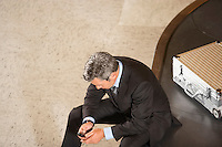 Business man with mobile phone sitting on luggage carousel in airport