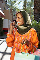 Portrait of muslim woman with shopping bags talking on mobile