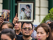 29 OCTOBER 2016 - BANGKOK, THAILAND:  A man holds a picture of the late Bhumibol Adulyadej, the King of Thailand, while he walks into the Grand Palace to homage to the King. Saturday was the first day Thais could pay homage to the funeral urn of the late Bhumibol Adulyadej, King of Thailand, at Dusit Maha Prasart Throne Hall in the Grand Palace. The Palace said 10,000 people per day would be issued free tickerts to enter the Throne Hall but by late Saturday morning more than 100,000 people were in line and the palace scrapped plans to require mourners to get the free tickets. Traditionally, Thai Kings lay in state in their urns, but King Bhumibol Adulyadej is breaking with tradition. His urn reportedly contains some of his hair, but the King is in a coffin,  not in the urn. The laying in state will continue until at least January 2017 but may be extended.      PHOTO BY JACK KURTZ