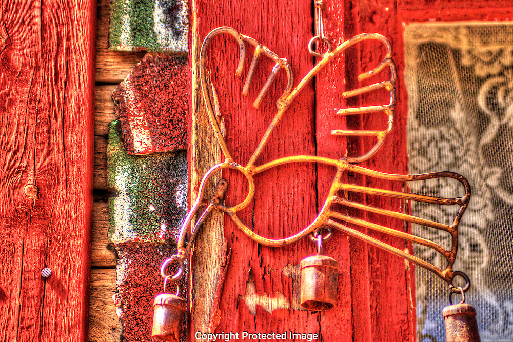 Handmade from yard junk this vintage Hummingbird wind chime hangs from the wall of an old miners shack in Chloride, Arizona.