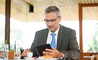 Österreich, Geschäftsmann mit Tablet Computer macht Kaffeepause in Restaurant